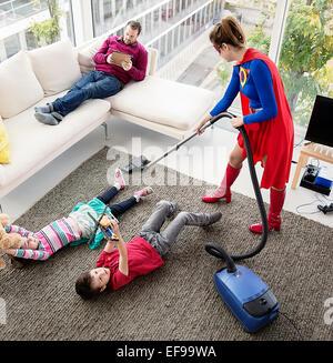 Superhelden-Familie im Wohnzimmer Staubsaugen - Stockfoto