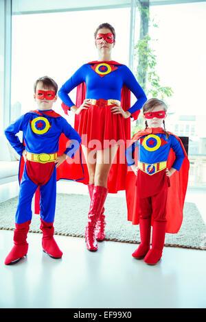 Superhelden-Mutter und Kinder im Wohnzimmer stehen - Stockfoto