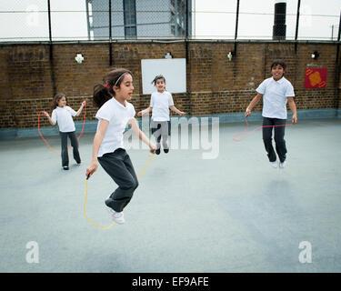 Mädchen in der Grundschule, London UK überspringen - Stockfoto