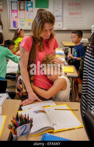 Eine Mutter tröstet ihre verängstigten Tochter am Tag der Eltern an einer Grundschule in Irvine, CA. Beachten Sie - Stockfoto