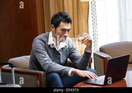 Junger Geschäftsmann mit Laptop im Hotelzimmer - Stockfoto