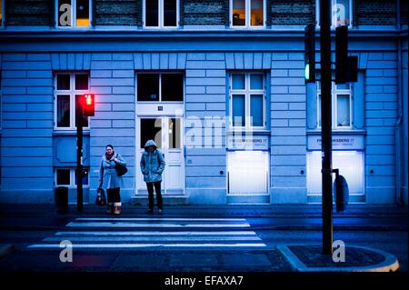 Zwei Menschen die Straße überqueren, in blauen Abend Licht Kopenhagen, Dänemark - Stockfoto