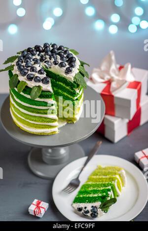 Folienschnitt Stück Grün Biskuit auf der Platte auf festlichen Hintergrund mit Bokeh Licht - Stockfoto