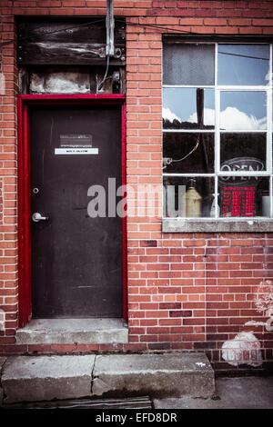 """Eine Tür und ein Fenster auf einem roten Backsteingebäude mit einem Zement bücken zu der Tür, und ein Schild """"geöffnet"""". - Stockfoto"""