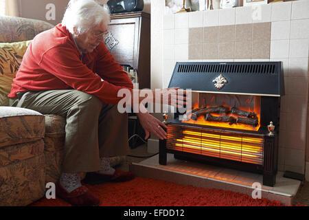 Im Alter von Rentner versucht, neben einer elektrischen Heizung warm zu halten - Stockfoto