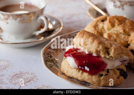 Ein Tisch für traditionelle englische Creme Tee. Marmelade und Gebäck mit einer Tischdecke und feines Porzellan - Stockfoto
