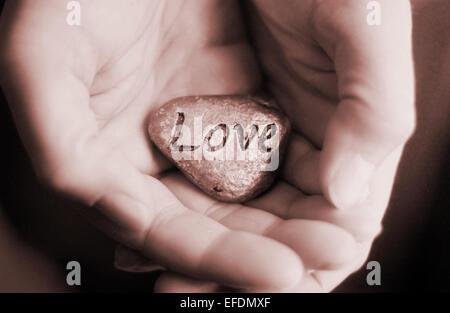 Hand mit Liebe Stein. Liebe und Fürsorge Konzept - Stockfoto