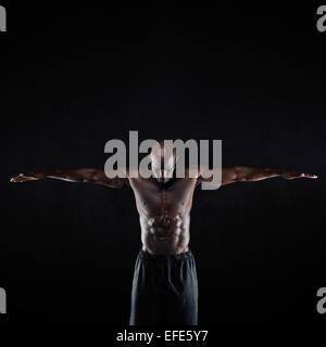 Porträt von einem Fit jungen muskulösen Mann streckte die Arme nach unten vor einem dunklen Hintergrund. Afrikanischer - Stockfoto
