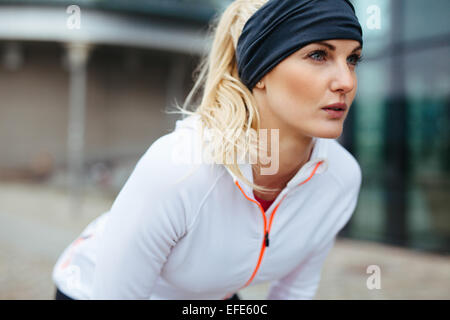 Junge Frau beugte sich über Sportausrüstung. Entschlossene Sport Frau sucht nach vorne laufen. - Stockfoto