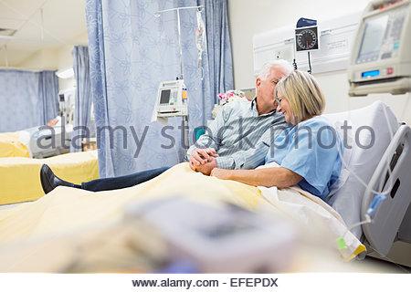 Mann, die Frau im Krankenhausbett beruhigend - Stockfoto