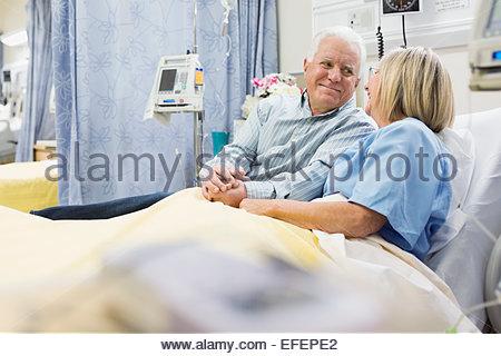 Mann und Frau, die Hand in Hand im Krankenhausbett - Stockfoto