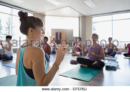 Ausbilder demonstriert Mudra in Yoga-Kurs - Stockfoto