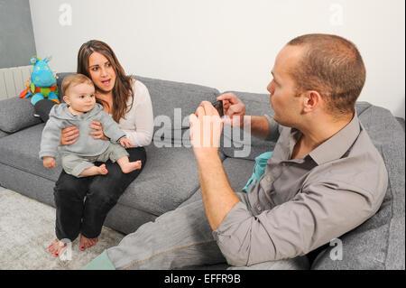 Vater unter Bild von Mutter und Sohn zu Hause - Stockfoto