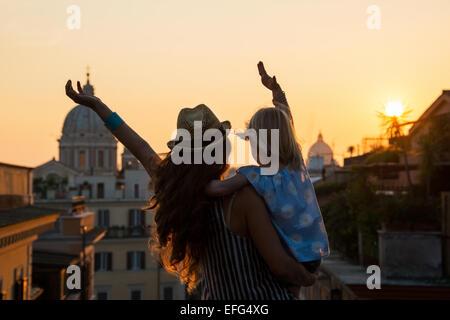 Silhouette von Mutter und Baby Mädchen auf der Suche auf den Dächern von Rom auf Sonnenuntergang und Freude. Rückansicht - Stockfoto