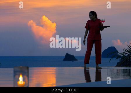 Six Senses Resort, Koh Yao Noi, Bucht von Phang Nga, Thailand, Asien. Kellnerin mit einem Glas Wein im Restaurant - Stockfoto