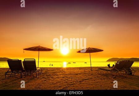 Retro-gefilterte Bild der Liegestühle und Sonnenschirme auf Sand bei Sonnenuntergang. Konzept für Erholung, Entspannung, - Stockfoto