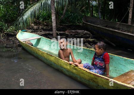 Kinder spielen in eines der lokale Boote von der Ngobe Indianer als ihre wichtigsten Transportmittel, geschützt unter einem provisorischen lean - verwendet