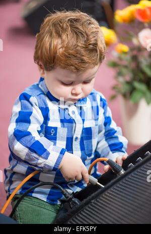 Kleiner Junge, ein Kabel in einen Lautsprecher - Stockfoto