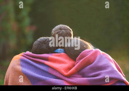 Geschwister, eingewickelt in eine Decke im Garten - Stockfoto