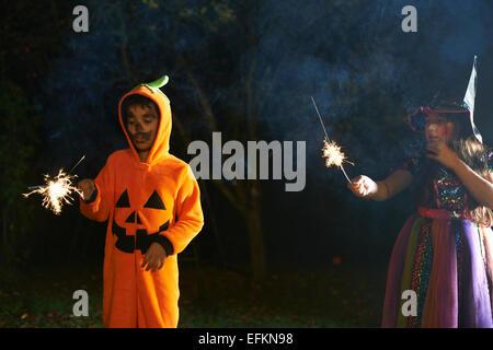 Bruder und Schwester Halloween Kostümen hält Wunderkerzen im Garten in der Nacht - Stockfoto
