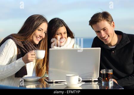 Gruppe von Freunden, die gerade eines Laptops in eine Restaurantterrasse am Strand im winter - Stockfoto