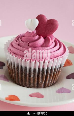 Marks & Spencer süsses Herz Cupcake auf Herzen Platte auf rosa Hintergrund - ideal für Valentinstag, Valentinstag - Stockfoto