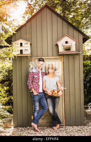 Porträt des Paares lehnte sich gegen Schuppen, junge Frau mit Apfelkorb - Stockfoto