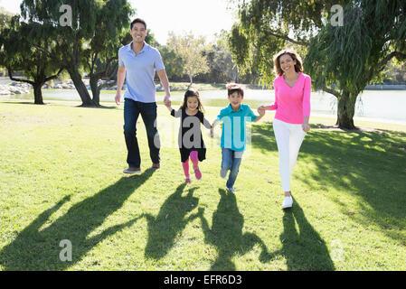 Älteres Paar und zwei Kinder laufen im Park Händen festhalten - Stockfoto