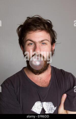 Mann bläst eine Kaugummi-Blase - Stockfoto