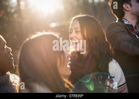 Lächelnde Gruppe von Freunden in einem sonnendurchfluteten Wald im Herbst stehen. - Stockfoto