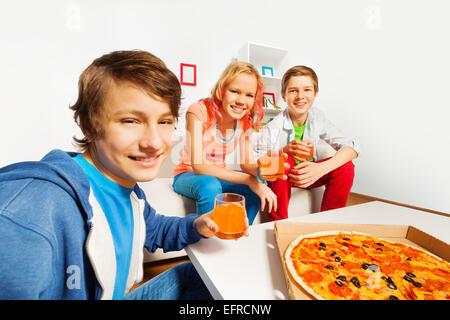 Positive Freunden halten Gläser und bereit für pizza - Stockfoto