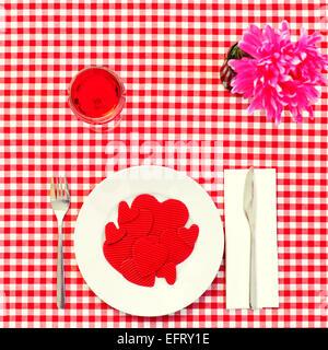 High-Angle Shot von einem Teller voller roten Herzen mit unterschiedlicher Größe auf einem gedeckten Tisch mit einer karierten rote und weiße Tischdecke