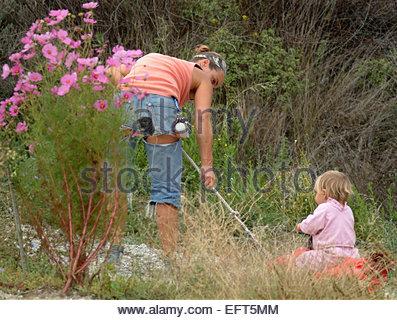 Einjähriges Kleinkind Boy Child (18-21 Monate) Portrait Mutter und Sohn spielen Pflanzen Blumen Spielzeug im Garten - Stockfoto