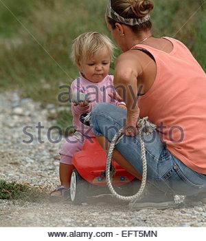 Einjähriges Kleinkind Boy Child (18-21 Monate) Portrait Mutter und Sohn spielen Spielzeug im Garten Reiten Spielzeug - Stockfoto