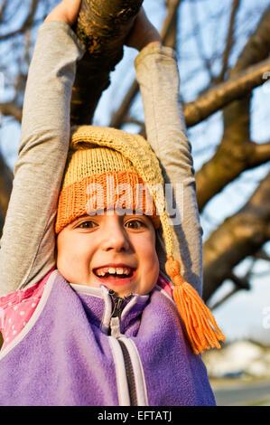 Junges Mädchen schwingen auf einem Ast im Herbst tragen gestrickte Zipfelmütze. - Stockfoto