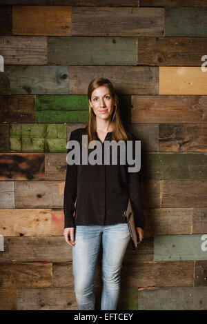 Porträt von attraktiven jungen Frau, die gegen einer Holzwand. Kaukasischen Frau in Casuals im Büro Blick in die - Stockfoto