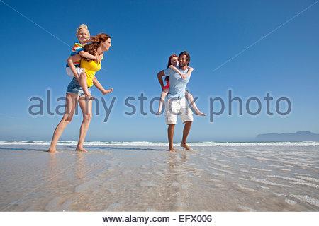 Mutter und Vater, geben zwei Kinder Huckepack, während am Sonnenstrand im Meer paddeln - Stockfoto