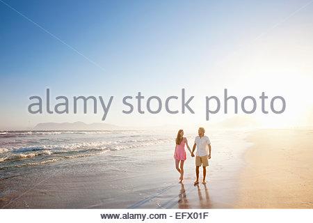 Paar, Hand in Hand, sonnigen Strand entlang spazieren - Stockfoto