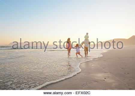 Glückliche Familie zu Fuß ins ferne halten Hände und Sohn mit Piggy-Backs, am sonnigen Strand - Stockfoto