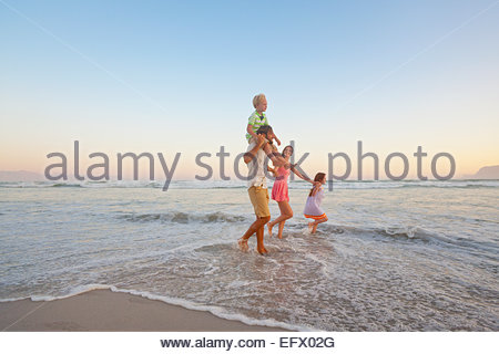 Glückliche Familie zu Fuß durch Wellen, halten Hände und Sohn mit Piggy-Backs, am sonnigen Strand - Stockfoto