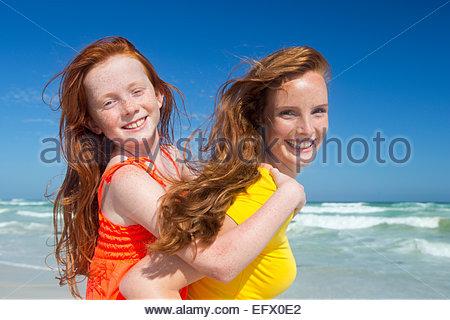Lächelnde Mutter gibt Tochter Huckepack am Sonnenstrand - Stockfoto