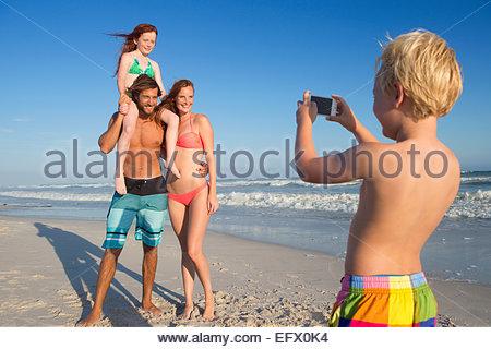 Jungen nehmen Foto von Mutter, Vater und Schwester am Sonnenstrand - Stockfoto