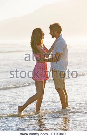 Romantisches Paar umarmen, in jeweils anderen Augen, am sonnigen Strand suchen - Stockfoto