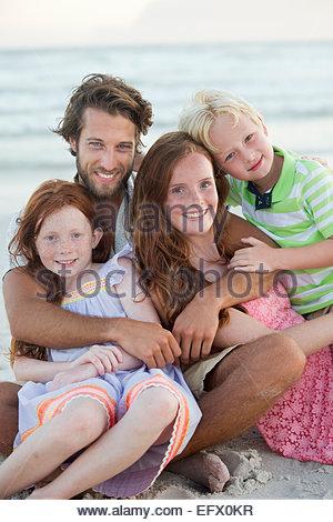 Porträt der Familie, lächelnd in die Kamera, umarmen am Sonnenstrand - Stockfoto