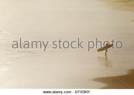 Surfer mit Surfbrett, vom Meer Strand entlang spazieren - Stockfoto