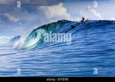 Surfer mit Helm Paddel über großen Surf-Welle in den Molukken, Indonesien - Stockfoto