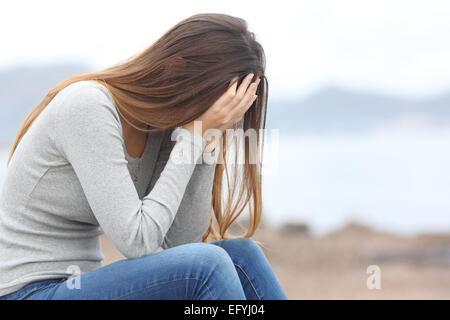 Besorgt Teenager Frau bedeckte ihr Gesicht mit Händen am Strand im winter - Stockfoto