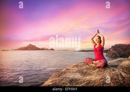Frau tun Meditation im roten Kostüm auf dem Stein in der Nähe des Ozeans in Gokarna, Karnataka, Indien - Stockfoto