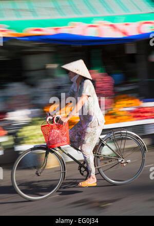 Frau Rad vorbei an Markt, Ben Tre, Mekong Delta, Vietnam - Stockfoto