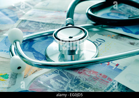 ein Stethoskop auf einen Haufen von Pfund Sterling Rechnungen, Darstellung der health care-Industrie-Konzept - Stockfoto